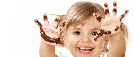 Niña con manos manchadas de chocolate